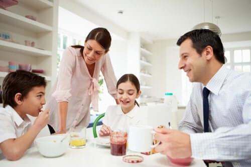 padre madre e figli sorridenti che fanno colazione