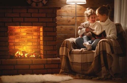 madre che legge alla figlia un libro di racconti per bambini seduta sulla poltrona davanti al camino