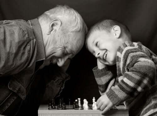 Nonno che gioca a scacchi col nipote felice