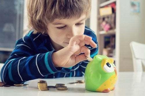 Bambino mette i soldi in un salvadanaio.