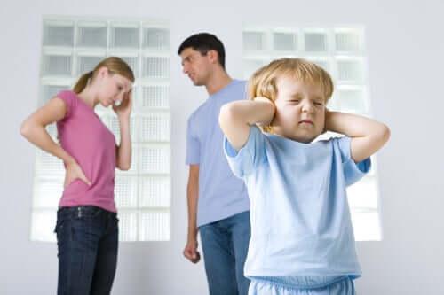 Aiutare il bambino durante il divorzio. Bambino che si tappa le orecchie perché i genitori litigano.