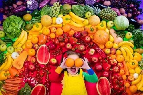 Bambina circondata da frutta e verdura