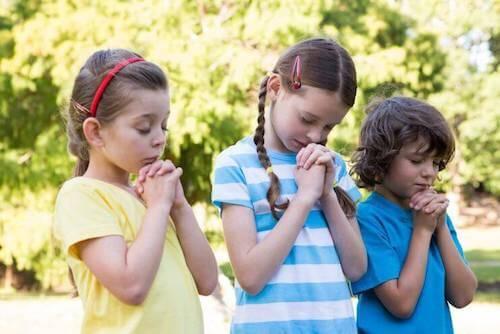bambine e bambino che pregano