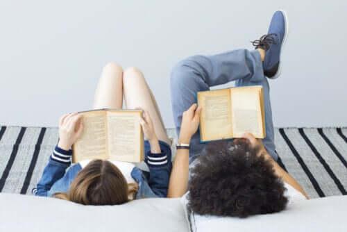 Due bambini leggono sdraiati sul letto.