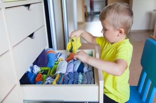 Bambino che mette in ordine il cassetto.