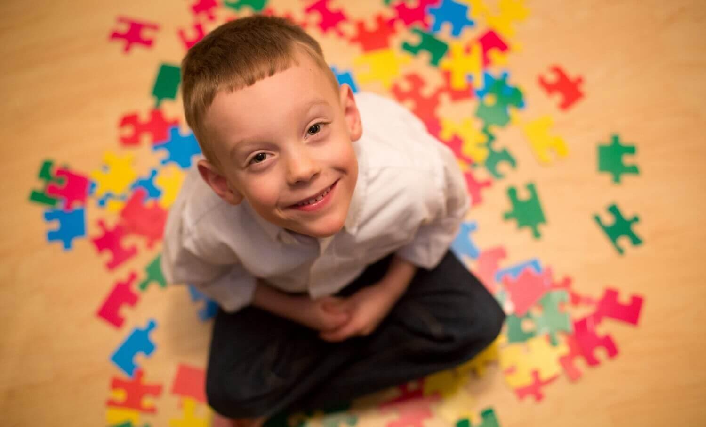 Bambino sorridente e pezzi di puzzle.