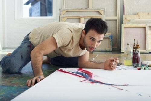 Ragazzo che dipinge un quadro per terra.