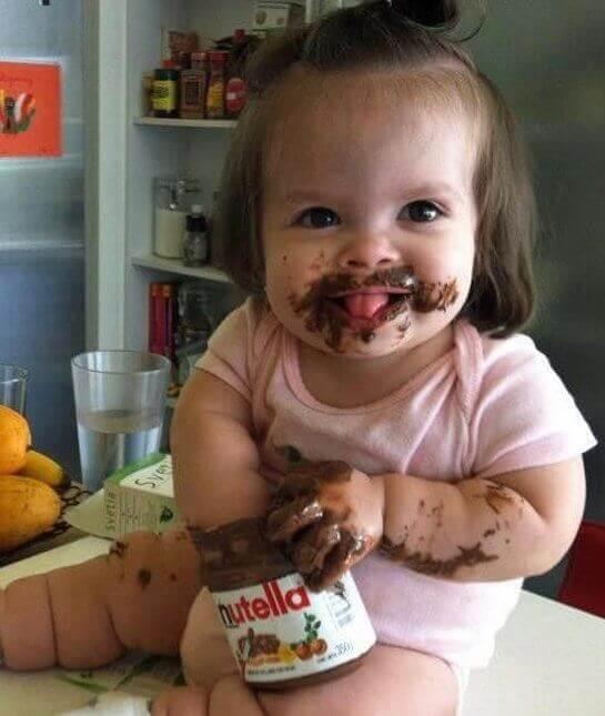 Situazioni divertenti con i bambini, bimba con le mani nella nutella.