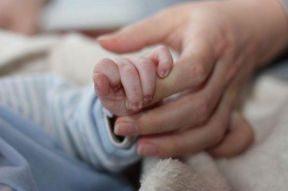 Mano di neonato stringe il dito della madre