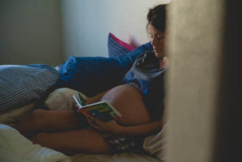 Donna incinta legge. Bebè dentro l'utero.