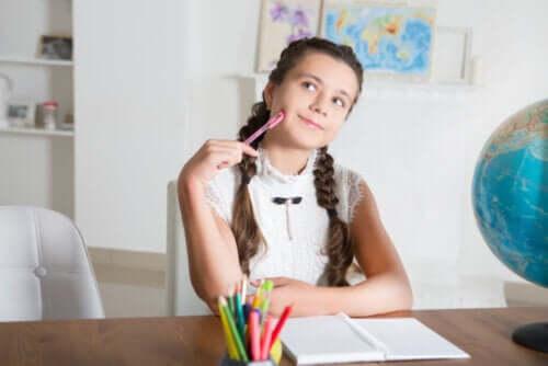 Bambina che pensa mentre studia