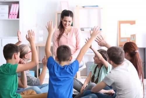 Bambini con mano alzata per rispondere alle domande della maestra.