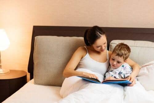 Avvicinare i bambini ai libri, madre e figlio leggono nel letto