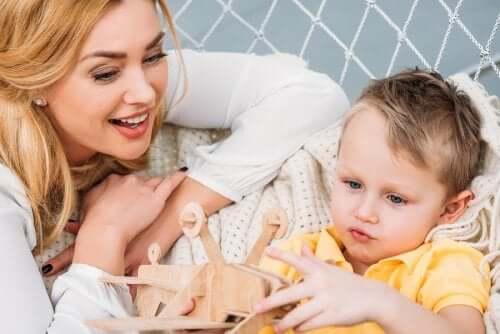 Bambino con giocattolo di legno e madre