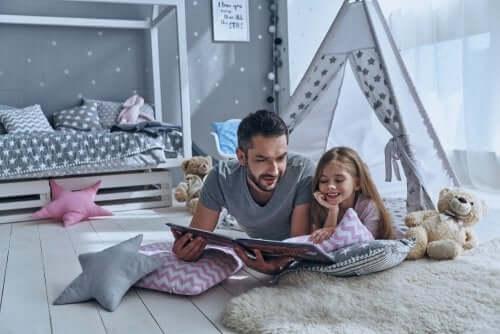 Padre e figlia leggono sdraiati a terra