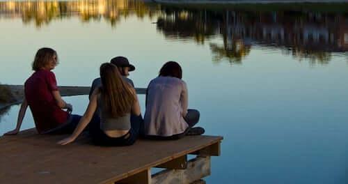 ragazzi seduti sulla banchina di un lago