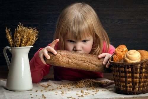 Bambina che guarda un pezzo di pane.