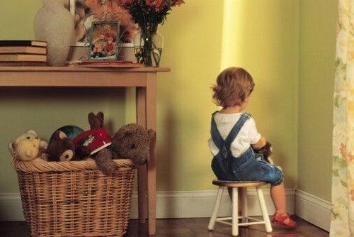 Bambini difficili: bambino seduto in un angolo in punizione
