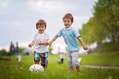 Bambini che giocano con la palla in un parco.
