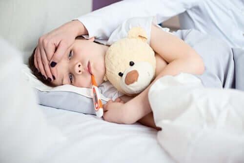 Bambino con orsetto e termometro.