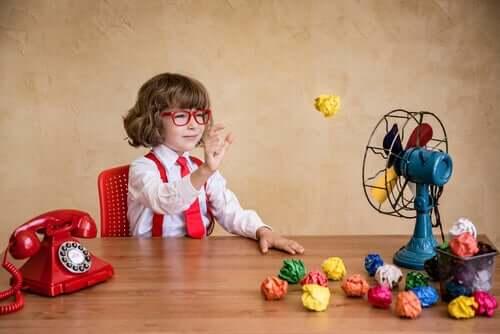 Bambino che gioca con delle palle di carta e un ventilatore.
