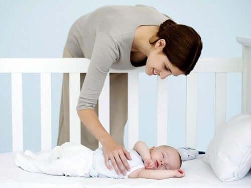 Mamma che accarezza neonato che dorme.