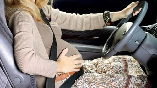 Guidare in gravidanza: donna guida col pancione.