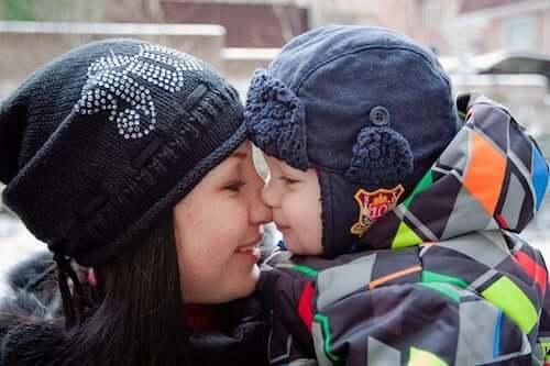 Figlio piccolo che bacia la mamma.