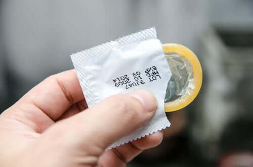 Mano con preservativo maschile
