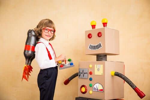 Bambino che gioca con un robot di cartone.