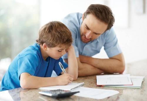 Padre che aiuta il figlio a fare i compiti: stili genitoriali.