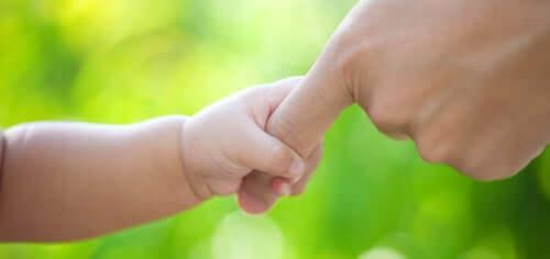 Neonato che tiene la mano del padre.