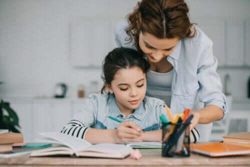 Bambina che fa i compiti con l'aiuto della mamma.
