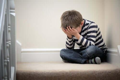 Bambino arrabbiato seduto in un angolo.