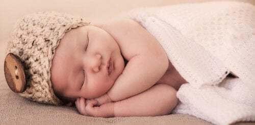 Bambino che dorme con un cappello in testa.