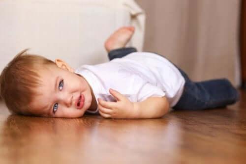 Bambino fa i capricci disteso sul pavimento