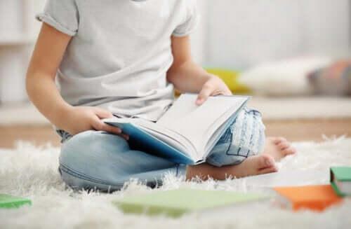 Bambino che legge  seduto per terra.
