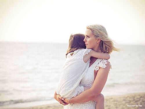 madre che tiene in braccio la figlia sulla spiaggia