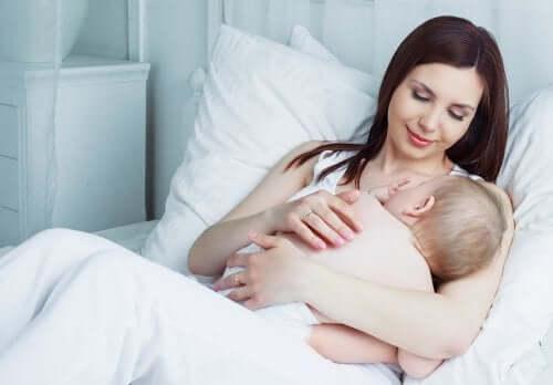 I grassi del latte materno e la crescita del neonato. Mamma che allatta in un letto bianco.
