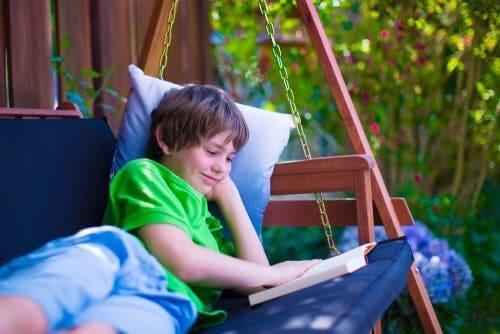 Ragazzo che legge un libro sul divano a dondolo