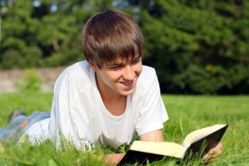 Ragazzo che legge un libro sdraiato sul prato