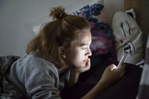 Tendenze pericolose sui social: ragazza usa un cellulare.