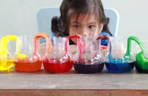 Bambina che gioca con acqua e colori