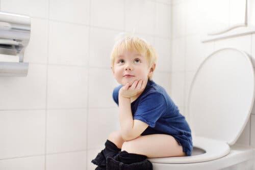 Bambino seduto sul water che fa la pipì