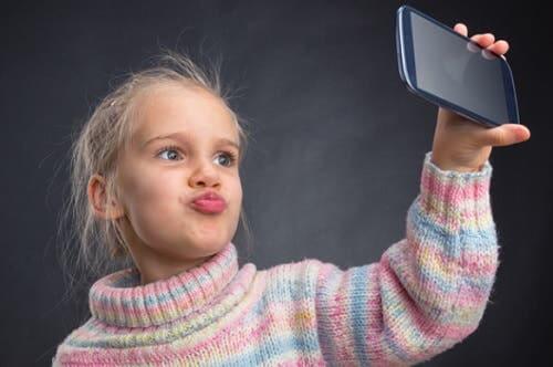 Bambina che si fa un selfie col telefono