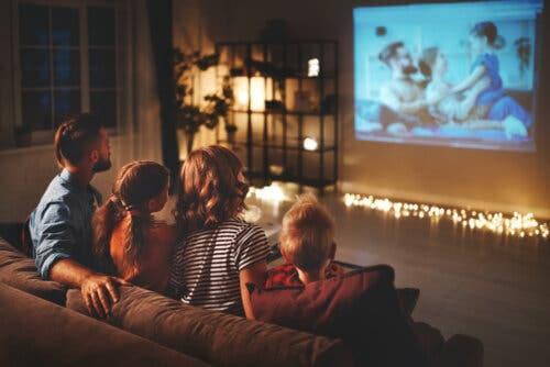 Famiglia seduta sul divano che vede un film per bambini