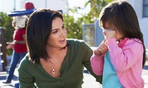 Fare troppo per i figli: mamma consola una bambina che piange