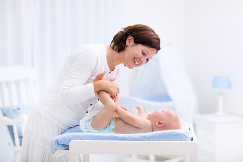 Mamma che cambia il neonato