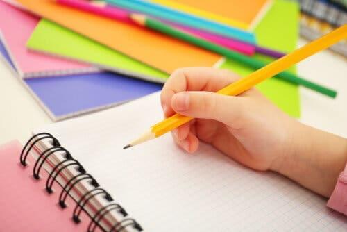 Bambino che scrive con la matita su un foglio di carta