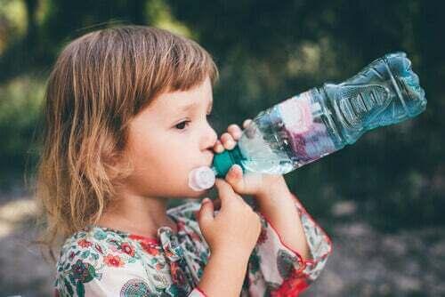 Bambina che beve acqua.